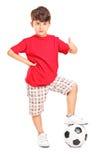 Caçoe com um futebol sob seu pé que dá um polegar acima foto de stock