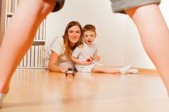 Caçoe comer uma maçã e o rolamento do carro do brinquedo com mamã Imagem de Stock