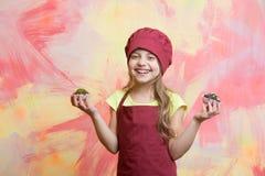 Caçoe, cozinheiro feliz da menina no chapéu vermelho do cozinheiro chefe, avental fotos de stock