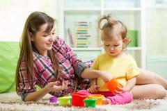 Caçoe a criança com a baby-sitter que joga no assoalho na sala imagem de stock