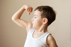 Caçoe a criança do menino que mostra o treinamento da força do punho dos músculos Foto de Stock Royalty Free