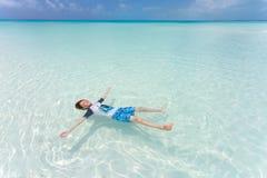 Caçoe a flutuação em uma parte traseira no mar bonito Imagem de Stock Royalty Free