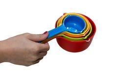Caçoe a mão do ` s que guarda o grupo de colheres de medição plásticas coloridas imagem de stock royalty free