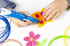 Caçoe a mão que guarda a pena azul da impressão 3d e que faz o artigo novo Foto de Stock