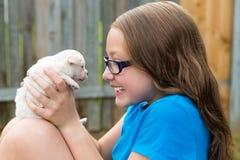 Caçoe a menina com o jogo da chihuahua do animal de estimação do cachorrinho feliz Fotografia de Stock