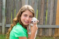 Caçoe a menina com o jogo da chihuahua do animal de estimação do cachorrinho feliz Imagem de Stock Royalty Free