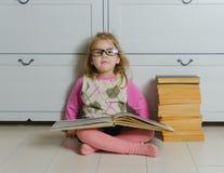 Caçoe a menina nos vidros com um livro que senta-se na leitura do assoalho imagens de stock royalty free
