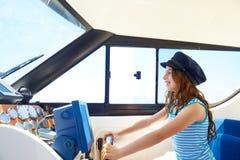Caçoe a menina que finge seja um tampão de marinheiro do capitão no barco Imagens de Stock Royalty Free
