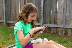 Caçoe a menina que toma fotos ao cão de cachorrinho com câmera Imagem de Stock