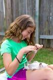 Caçoe a menina que toma fotos ao cão de cachorrinho com câmera Foto de Stock