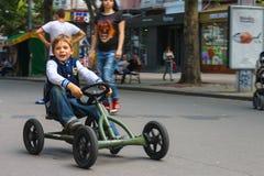 Caçoe na área de jogo que monta um carro do brinquedo Nikolaev, Ucrânia Fotos de Stock