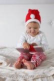 Caçoe no chapéu de Santa com presente de Natal da tabuleta, luz, Imagens de Stock Royalty Free