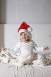 Caçoe no chapéu de Santa que joga na casa da cama, luz, Year& novo x27; concep de s Fotografia de Stock Royalty Free