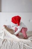 Caçoe no chapéu de Santa que joga na casa da cama, luz, Year& novo x27; concep de s Imagem de Stock