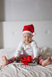 Caçoe no chapéu de Santa que joga na casa da cama, luz, Year& novo x27; concep de s Imagens de Stock Royalty Free