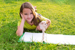 Caçoe o cão da menina e de cachorrinho nos trabalhos de casa que encontram-se no gramado Imagem de Stock Royalty Free