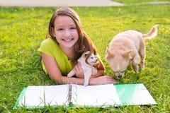 Caçoe o cão da menina e de cachorrinho nos trabalhos de casa que encontram-se no gramado Fotografia de Stock