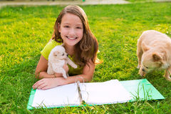 Caçoe o cão da menina e de cachorrinho nos trabalhos de casa que encontram-se no gramado Fotos de Stock