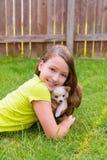 Caçoe o encontro feliz do cão da menina e de cachorrinho no gramado Foto de Stock