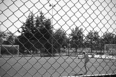 Caçoe o jogo do futebol em um campo de jogos em um parque cercado por uma rede de arame em preto e branco para o maior drama apen Fotos de Stock