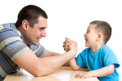 Caçoe o menino e o paizinho que competem na força física foto de stock