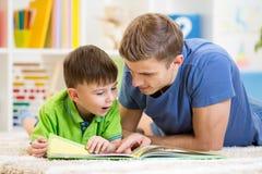 Caçoe o menino e seu pai leu um livro no assoalho em casa Fotografia de Stock Royalty Free