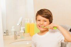 Caçoe o menino feliz escovar os dentes na manhã fotografia de stock royalty free