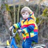 Caçoe o menino no capacete de segurança e na bicicleta colorida da equitação da capa de chuva Fotografia de Stock Royalty Free