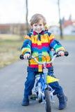 Caçoe o menino no capacete de segurança e na bicicleta colorida da equitação da capa de chuva Imagens de Stock Royalty Free