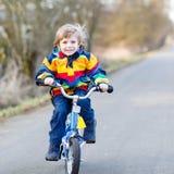 Caçoe o menino no capacete de segurança e na bicicleta colorida da equitação da capa de chuva, outd Fotografia de Stock Royalty Free