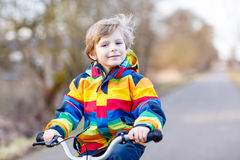 Caçoe o menino no capacete de segurança e na bicicleta colorida da equitação da capa de chuva, outd Imagem de Stock Royalty Free