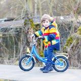 Caçoe o menino no capacete de segurança e na bicicleta colorida da equitação da capa de chuva, outd Imagens de Stock Royalty Free