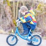 Caçoe o menino no capacete de segurança e na bicicleta colorida da equitação da capa de chuva, outd Fotografia de Stock