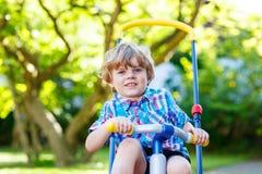 Caçoe o menino que conduz o triciclo ou a bicicleta no jardim Fotografia de Stock Royalty Free