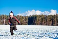 Caçoe o menino que funciona no inverno Fotos de Stock Royalty Free