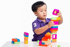 Caçoe o menino que joga com blocos do construtor do brinquedo isolado Fotografia de Stock