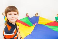 Caçoe o menino que joga o paraquedas do arco-íris com seus amigos Fotos de Stock Royalty Free