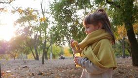 Caçoe os jogos no parque do outono, bolhas de sabão de sopro da criança fêmea em árvores do fundo vídeos de arquivo