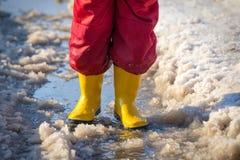 Caçoe os pés nos rainboots que estão na poça do gelo Imagem de Stock