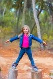 Caçoe troncos de árvore de escalada da menina com braços abertos Imagem de Stock Royalty Free