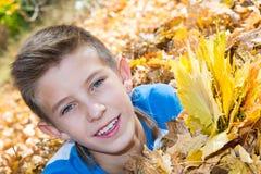 Caída Adolescente del muchacho con las hojas en otoño Foto de archivo
