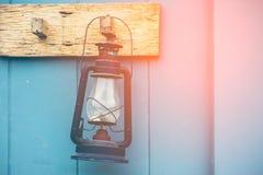 Caída ardiente de la lámpara de keroseno en la pared de madera Imagen de archivo