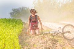 Caída bonita de la muchacha apenas de la bici de la bicicleta cerca del campo de trigo en los rayos solares La bicicleta miente e Fotos de archivo libres de regalías