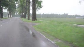 Caída de la lluvia en la impulsión del parabrisas del automóvil del coche en el camino almacen de metraje de vídeo
