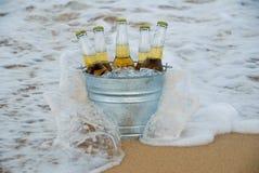 Caída de las ondas contra un compartimiento de cerveza helada Imagenes de archivo