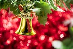 Caída del ornamento de la campana de la Navidad en rama de árbol con el backg rojo del bokeh Imagen de archivo libre de regalías