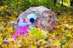 Caída Muchacha linda del niño que juega con las hojas caidas en otoño Foto de archivo