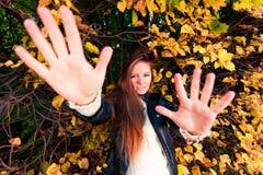 Caída Muchacha que miente en las hojas en bosque otoñal del parque Fotos de archivo libres de regalías