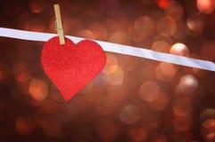 Caída roja del corazón del brillo sobre fondo marrón del bokeh Imagen de archivo