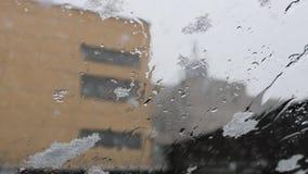 Caídas de la nieve fuera de la ventanilla del coche Descensos sobre el vidrio metrajes